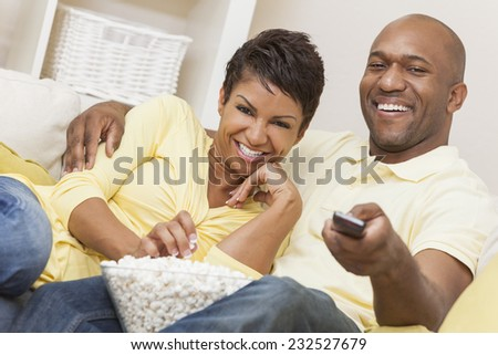 A happy African American man and woman couple in their thirties sitting at home using a remote control, eating popcorn and watching a movie or television - stock photo