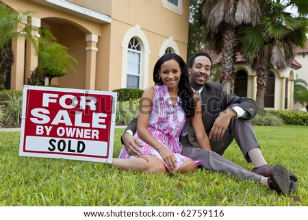 A happy African American man and woman couple outside a large house with a For Sale Sold sign - stock photo
