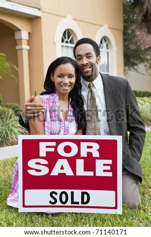 A happy African American man and woman couple outside a large house with a For Sale Sold sign celebrating the purchase of a property - stock photo