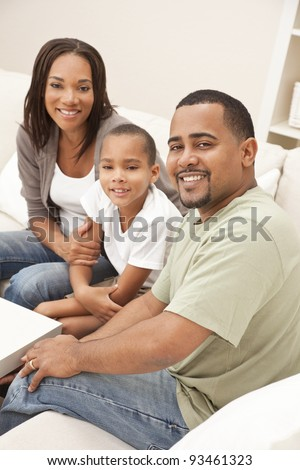 A happy African American man, woman and boy, father, mother and son, family sitting together at home - stock photo