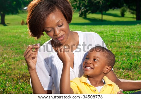 a happy african american mom poses with her son - stock photo