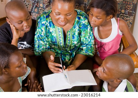 a happy african mother reading a book to her 4 children in living room - stock photo