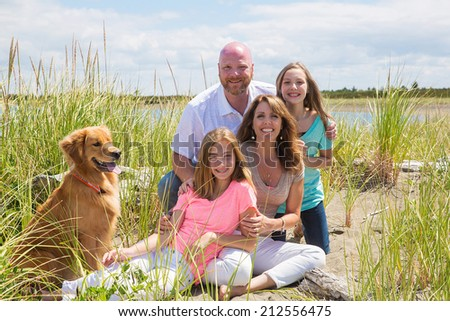A happy American family on vacation at the beach with their golden retriever dog