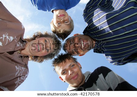 a happy American-German family with mother, father and their two sons, photographed from down towards sky with flashlight with blue sky and clouds in the background - stock photo