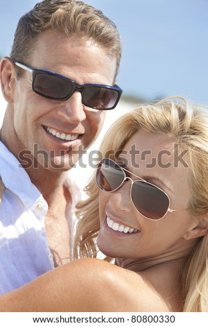A happy and attractive man and woman couple wearing sunglasses and smiling in sunshine at the beach - stock photo