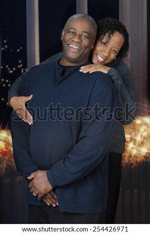A happy and attractive, mature African American couple before nighttime windows and white Christmas lights. - stock photo