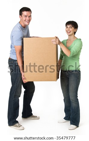 A happy and attractive young couple holding a cardboard box together.  They are smiling and are looking directly at the camera.  Vertically framed shot.