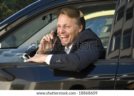 A happy and handsome forties businessman enjoys a lighthearted conversation on his cellphone while sitting in his parked car