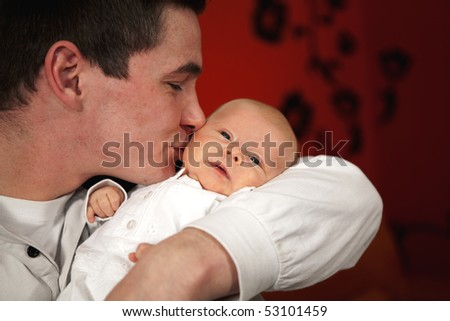 a happy and proud young father holding and kissing his 7 weeks old daughter