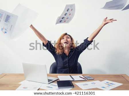 A happy and successful business woman with her arms raised working with a laptop.