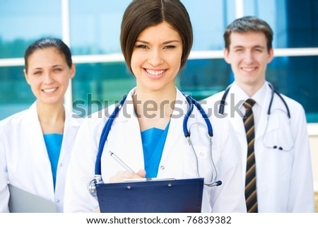 A happy and successful medical team outside hospital building - stock photo