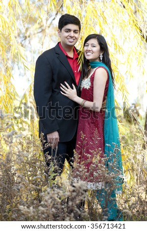 A happy and young Indian couple posing under a willow tree on a sunny day in the fall. - stock photo