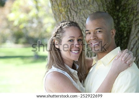 A happy and young Interracial couple posing on a sunny day under a tree - stock photo