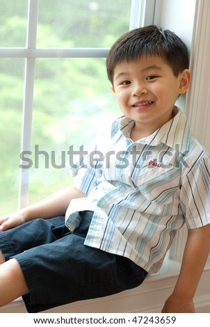 A happy Asian boy smiling and posing by a large window.