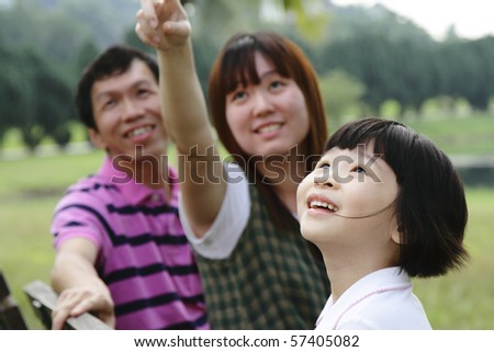 A happy Asian family at a park - stock photo