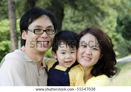 A happy Asian family at a public park - stock photo