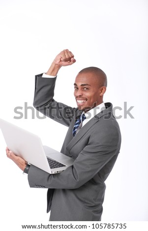 A happy attractive African American businessman wearing a corporate grey suit and blue tie holding a laptop computer, raising his fist up and punching the air in a triumphant move in a successful deal