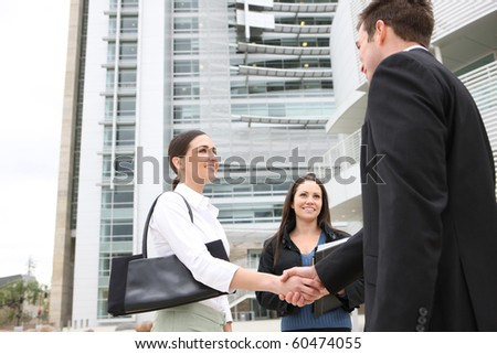 A happy attractive man and woman business team handshake at office building