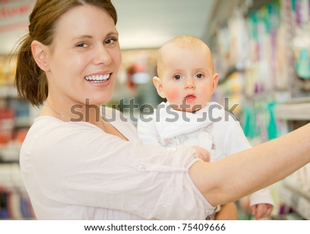 A happy baby and mother in a grocery store buying groceries - stock photo