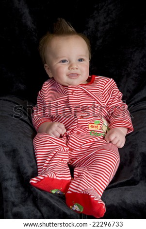 A happy baby boy in a christmas outfit.