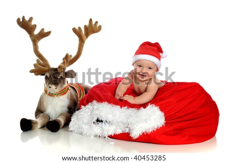 A happy baby boy in a Santa hat laying on his filled sack next to a plush reindeer.  Isolated on white. - stock photo
