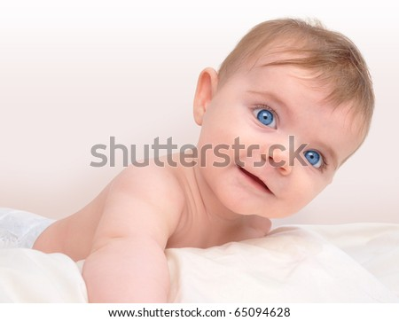A happy baby boy or girl is laying on a white blanket looking into the camera and smiling. The child has bright blue eyes and there is a faded background for a text area. - stock photo