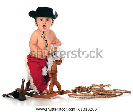 A happy baby boy shouting as he rides his rocking horse.  Isolated on white. - stock photo