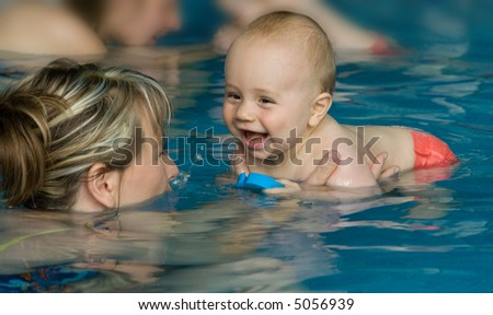 A happy baby enjoying first swim with mother.