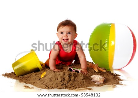 A happy baby girl crawling over a sand pile with beach toys, sunglasses and seashells nearby. - stock photo