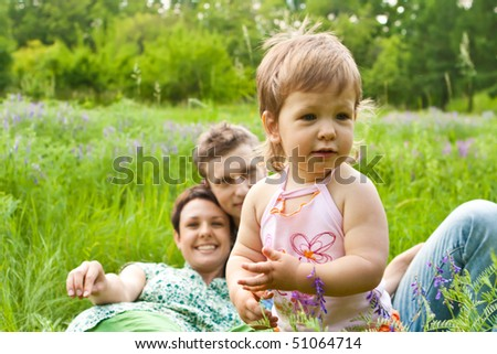A happy baby girl in the meadow, parents looking at her - stock photo
