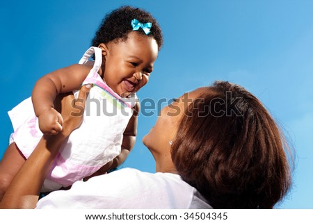 a happy baby held in the air - stock photo