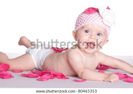 A happy baby is laying in some rose pedals. - stock photo