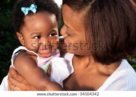 a happy baby looks at her mother - stock photo