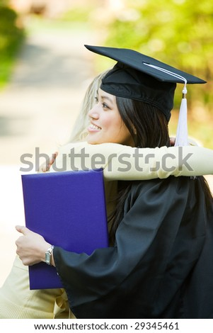 A happy beautiful graduation girl being congratulated by her friend - stock photo
