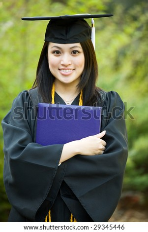A happy beautiful graduation girl holding her diploma - stock photo