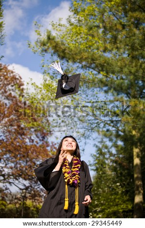A happy beautiful graduation girl throwing her cap in the air - stock photo