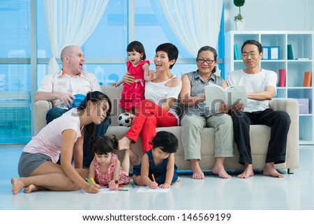 A happy big family sitting on the sofa and posing at camera - stock photo