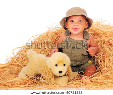 A happy, biracial baby boy in overalls playing in a pile of hay with his toy pup.  Isolated on white.