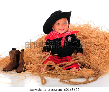 A happy biracial baby dressed as a cowboy sitting in a pile of hay.  Isolated on white. - stock photo