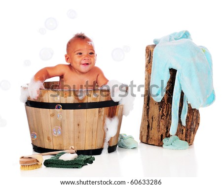 A happy biracial baby having a bubble bath in a wooden tub.  Isolated on white. - stock photo