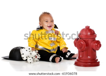 A happy biracial baby in a fireman's outfit, sitting by a fire hydrant with his hat, a hose and a toy  Dalmatian.  Isolated on white.