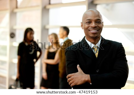 A happy black business man with people in the background - stock photo