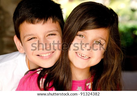 a happy brother and sister smiling for their portrait - stock photo