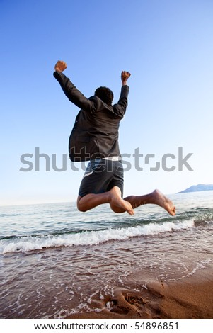 A happy business man jumping by the ocean - happy successful concept