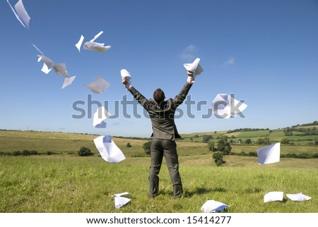 A happy businessman lets go of this paperwork! - stock photo