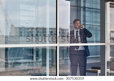 A happy businessman looking out the window while talking on his cellphone - stock photo