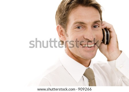 A happy businessman talking on a phone