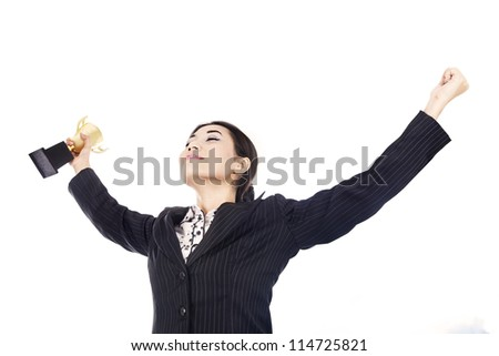 A happy businesswoman celebrating her winning holding the trophy isolated over white - stock photo