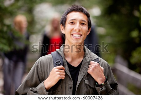 A happy camper smiling at the camera with a backpack outdoors - stock photo