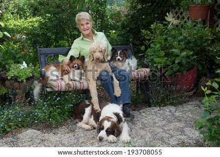 A happy casual portrait of an elderly woman and her four dogs in a peaceful country garden. - stock photo
